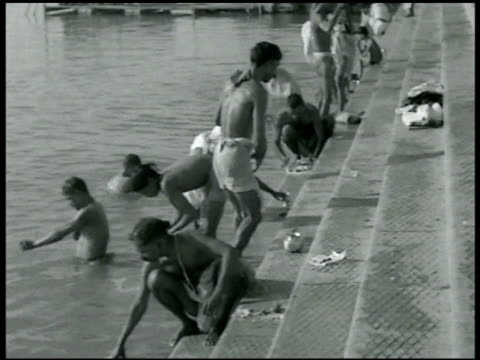 Men washing laundry themselves at base of waterfront steps in the Ganges River Sacred pilgrimage
