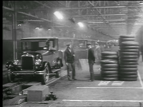 stockvideo's en b-roll-footage met b/w 1927 men watch as cars are driven off assembly line in factory / new york state - 1927