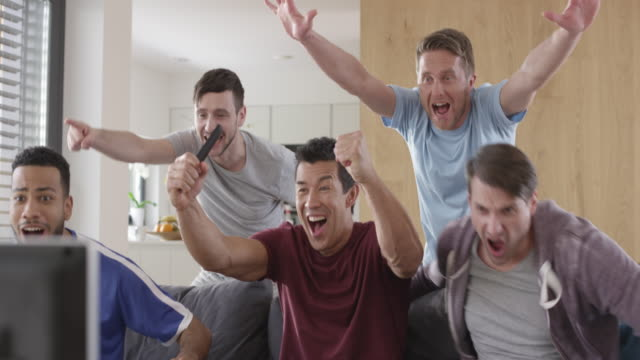men watching a football match and celebrating a goal - living room stock videos & royalty-free footage