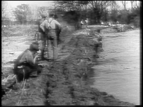 B/W 1927 men watching as Mississippi River flood waters cause levee to collapse / newsreel / slate