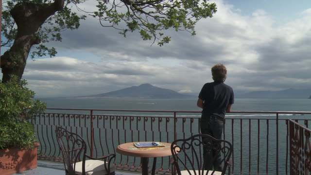 stockvideo's en b-roll-footage met   ws men watching mount vesuvius and cruise passengers in front of mount vesuvius / sorrento, campania, italy - afweren