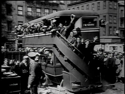 vídeos y material grabado en eventos de stock de men waving from a double-decker bus / men waving from a bus with barred windows / train pulling into a station / buses driving down a dirt road - 1934