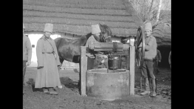 men wearing bucket-shaped helmets with horses at a deep well with a man turning a hand crank; others work a larger, more modern pump with a large... - austria video stock e b–roll