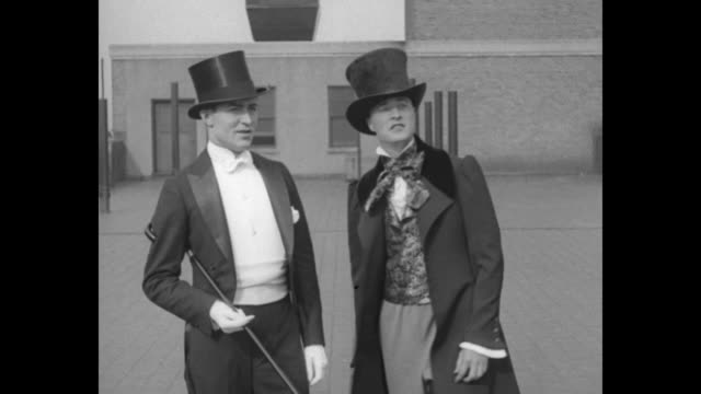 men wearing costumes of formal dress of different eras / a man in top hat and tails talks to another wearing 19th century apparel / a young dandy... - cravat stock videos and b-roll footage
