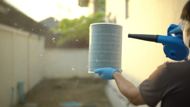 men wearing glove and protection glasses cleaning the air filter by a blower - purity stock videos & royalty-free footage