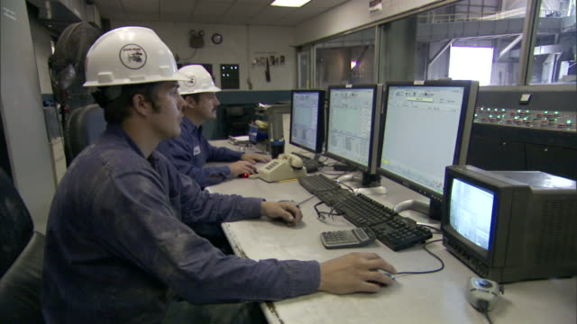 men wearing hard hats work on computers inside a factory. - control room stock videos & royalty-free footage