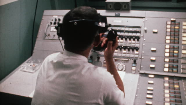 men wearing headsets and talking on telephones monitor a control panel while viewing a rocket launch on television screens. - control room stock videos & royalty-free footage