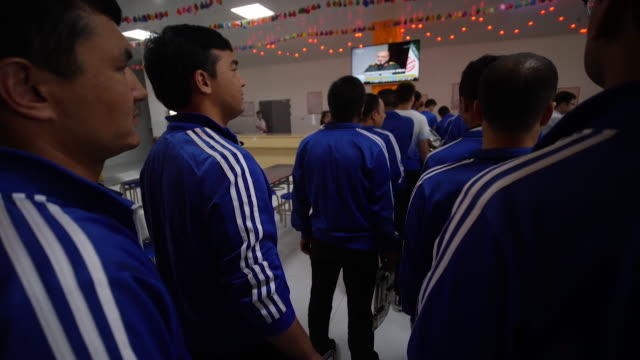 men wearing matching uniforms queuing in canteen up at secure reeducation facility in xinjiang for muslim ethnic groups promoted by china as schools... - prison education stock videos & royalty-free footage
