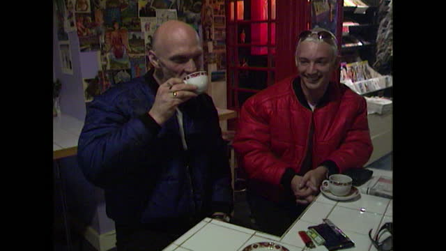 men wearing puffer jackets drink tea or coffee in a café or shop where another man browses or restocks shelves and view inside a restaurant showing... - coffee drink stock videos & royalty-free footage