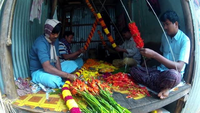 Men weave flower garlands at Kolkata Flower Market.
