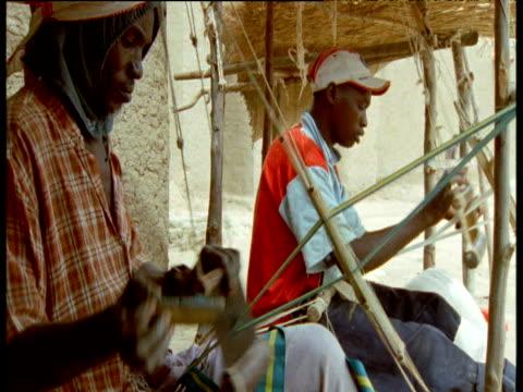 Men weaving on looms in street, Djenne