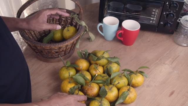 テーブルの上にオレンジを選ぶ男性 - 荒い麻布点の映像素材/bロール