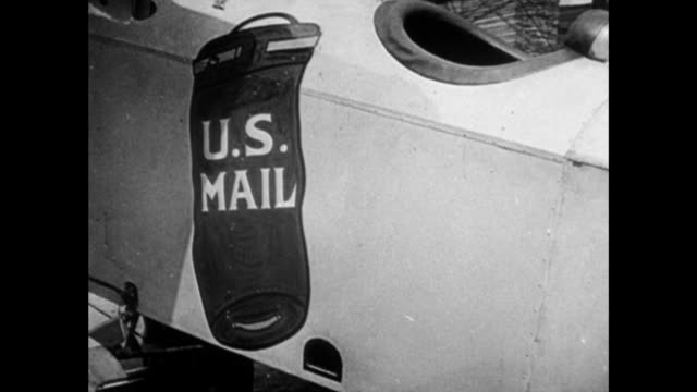 men wind the propeller of airmail plane / in 1953, william boeing discusses his role in international mail service / 'in 1919 eddie hubbard and i... - united states postal service stock videos & royalty-free footage