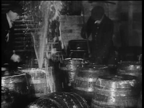 b/w 1932 men with axes destroying barrels of beer / beer spraying out of barrels / chicago - anno 1932 video stock e b–roll