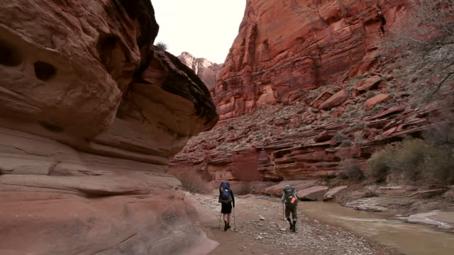 men with backpacks hiking along river edge in red rock desert canyon landscape. - スロット渓谷点の映像素材/bロール