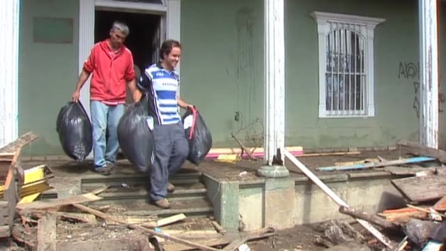 men with bin bags filled with rubbish leave destroyed house following devastating earthquake in chile; 4 march 2010 - müllsack stock-videos und b-roll-filmmaterial