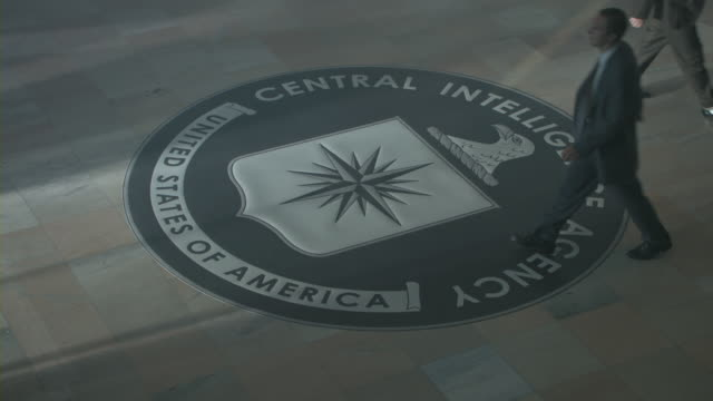 Men with briefcases passing by the CIA emblem.