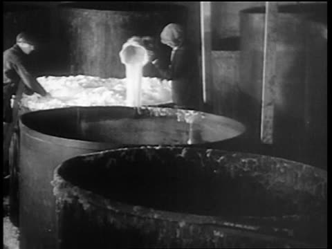 b/w 1932 men with buckets scooping out pouring on floor foamy beer from giant vat / chicago - anno 1932 video stock e b–roll