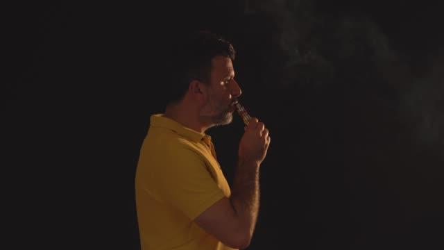黒の背景に電子タバコを持つ男性 - 煙草製品点の映像素材/bロール