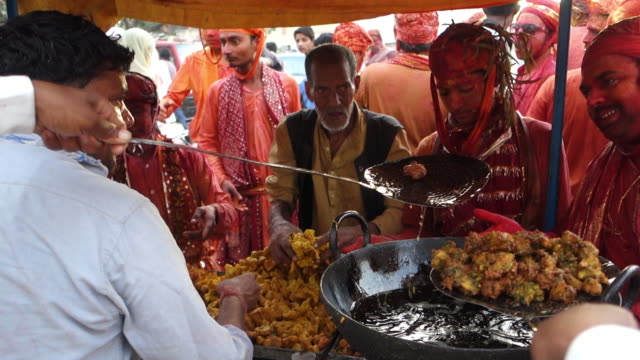 men with faces painted red waiting at indian market stand for food - market stall stock videos & royalty-free footage