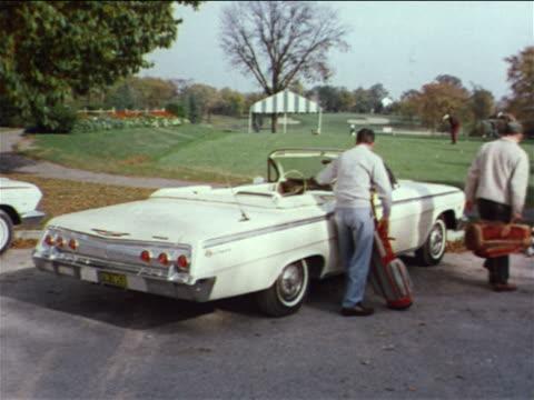 vídeos de stock, filmes e b-roll de 1962 rear view 2 men with golf clubs walking from convertible towards golf course / industrial - bolsa de golfe