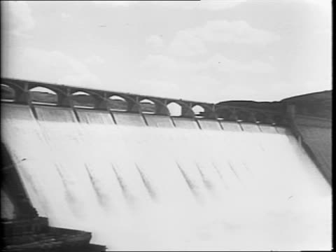Men with hard hats walking past the camera / man operating a switchboard / water flowing through the Coulee Dam / closer view of the Coulee Dam /...
