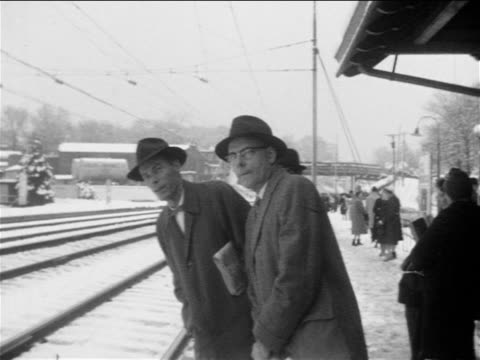 b/w 1955 2 men with hats + coats waiting + looking for train at snowy train platform / narberth, pa - shrugging stock videos and b-roll footage
