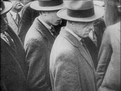 b/w 1927 men with hats standing on street / newsreel - 1927年点の映像素材/bロール