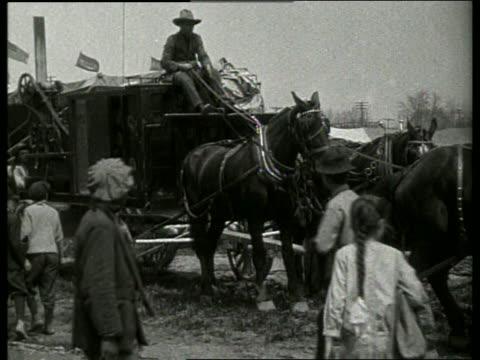 b/w men with horse drawn tent stakedriving machinery / 1910's / no sound - 草食性点の映像素材/bロール