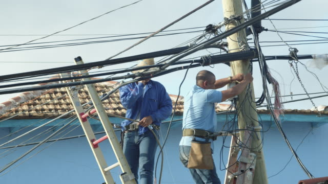 men with limited protective gear working on electricity, tv or phone wires in trinidad, cuba - health and safety stock videos & royalty-free footage