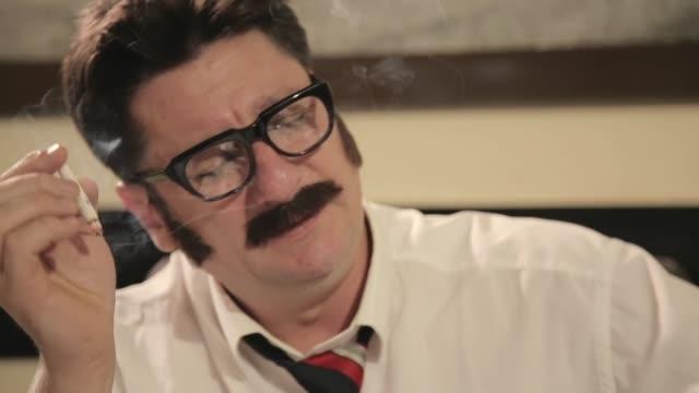 vidéos et rushes de les hommes avec des moustaches et des verres fume la cigarette, raccrochant un téléphone, tout en s'asseyant sur un bureau - détective