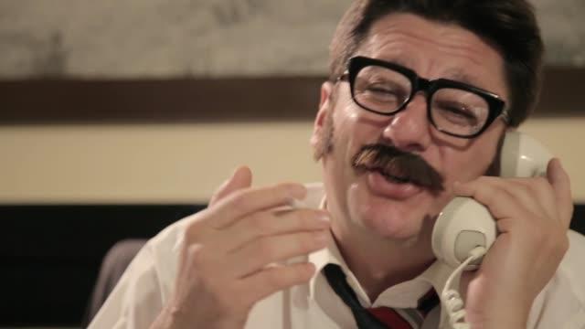 vidéos et rushes de les hommes avec des moustaches et des verres fume la cigarette, parlant sur un téléphone rétro, tout en s'asseyant sur un bureau - détective