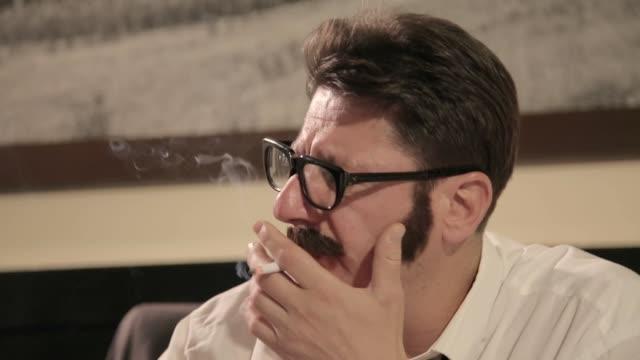 vidéos et rushes de les hommes avec des moustaches et des verres fume la cigarette tout en s'asseyant sur un bureau - chemise et cravate