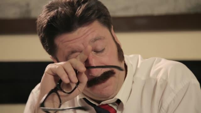 vidéos et rushes de hommes avec des moustaches prenant des lunettes, tout en s'asseyant sur un bureau - détective