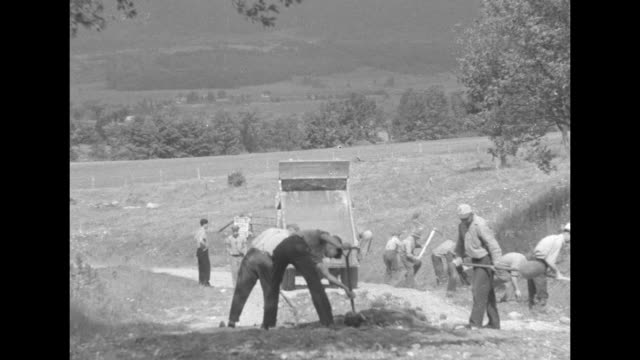 vs men with pickaxes dig trench along concrete road / men on unpaved country road spread dirt dumped by truck / men dump bags of cement into mixer /... - new deal stock-videos und b-roll-filmmaterial