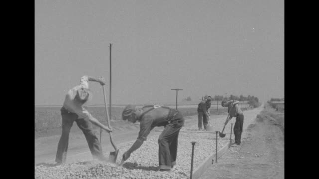 men with shovels and rakes prepare gravel in roadbed through countryside; some wear spiked shoes / vs compactor machine on city street and country... - roadworks stock videos & royalty-free footage