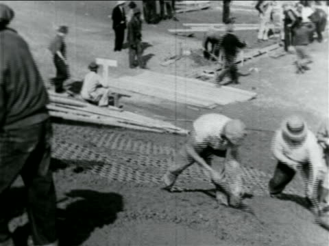 b/w 1934 men with shovels laying cement on hillside in wpa construction project / documentary - anno 1934 video stock e b–roll