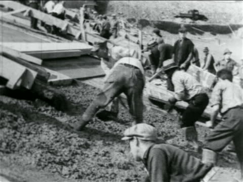B/W 1934 men with shovels laying cement on hillside in WPA construction project / documentary
