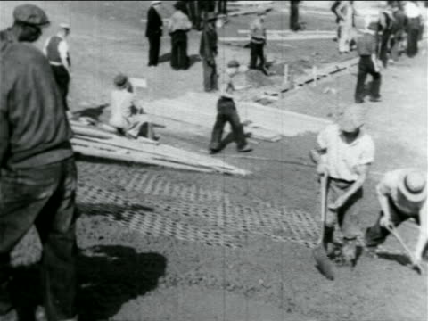 stockvideo's en b-roll-footage met men with shovels laying cement on hillside in wpa construction project / documentary - 1934