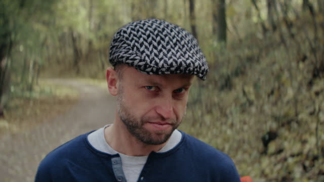 men with solemn face standing in forest - flat cap stock videos & royalty-free footage