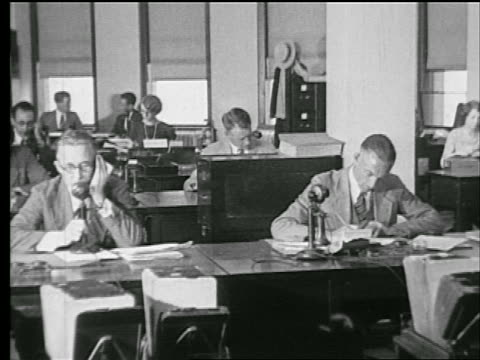 B/W 1927 men + woman sitting at desks in office / one man on telephone / industrial