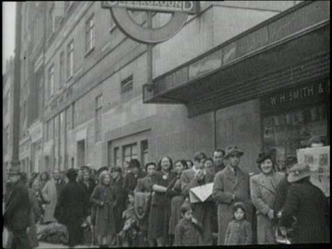 Men women and children wait in line for entrance into an air raid shelter in a London subway