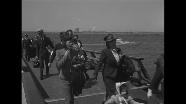 men, women, children and crew of a pan american clipper walk from a floating dock / actor robert montgomery waves to camera - passenger stock videos & royalty-free footage