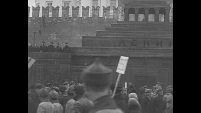 vidéos et rushes de men, women, children march past kremlin and tomb of lenin, some carry flags, all wear heavy coats and winter hats during moscow patriotic... - moscou