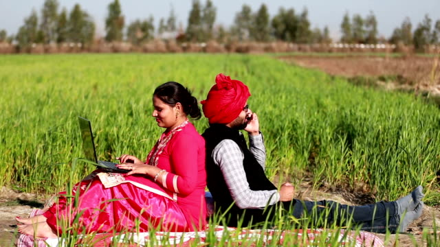 men & women portrait in the green field using laptop & smartphone - turban stock videos & royalty-free footage