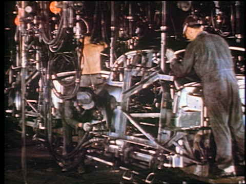 1947 3 men work on car frame in assembly line / robot machinery passes in foreground / industrial - automobile industry stock videos & royalty-free footage