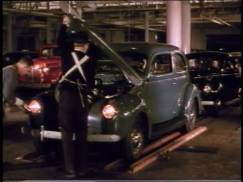 stockvideo's en b-roll-footage met 1940 men work on ford on assembly line then drive away - automobile industry