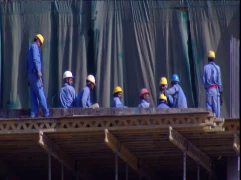 men work on gantry in construction site dubai - erezione video stock e b–roll