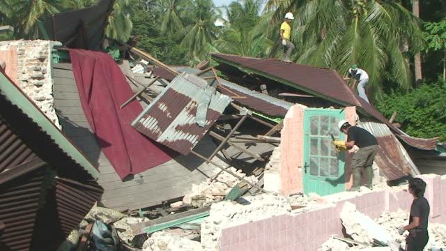 vídeos y material grabado en eventos de stock de men working amongst rubble after earthquake in downtown padang, sumatra / audio - isla de sumatra