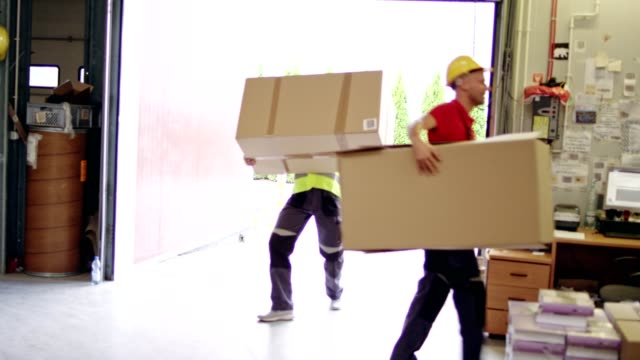 Men working at a warehouse. Carrying heavy boxes